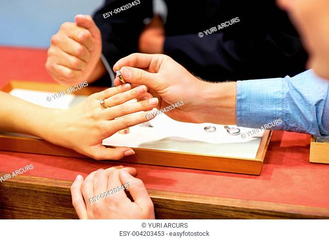 Cropped image of a woman trying on an engagement ring with her fiancee holding another ring