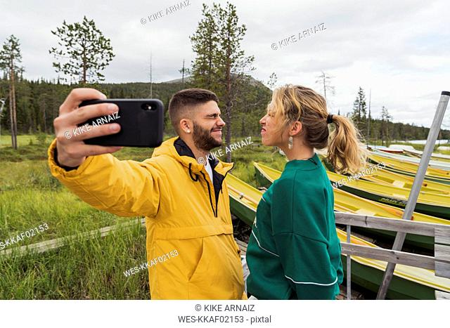Finland, Lapland, young couple taking a funny selfie at the lakeside
