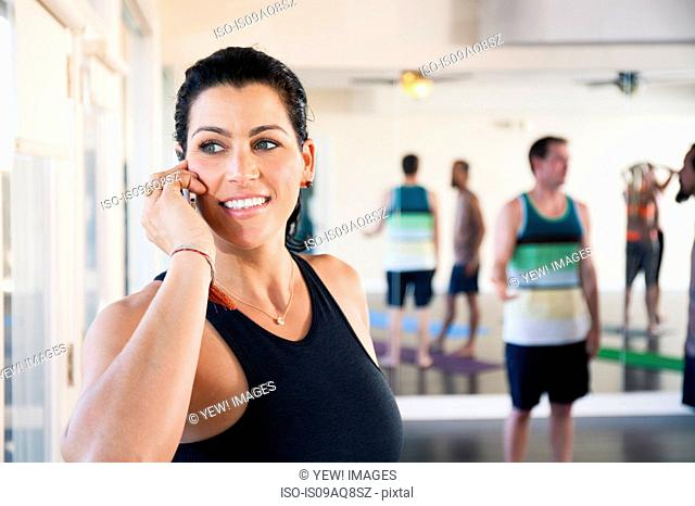 Mid adult woman on cell phone in exercise studio
