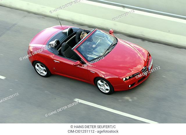 Alfa Romeo Spider 2.2 JTS Exclusive, model year 2007-, red, driving, diagonal from the front/oben, country road, open top