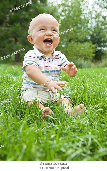 Baby sitting in grass