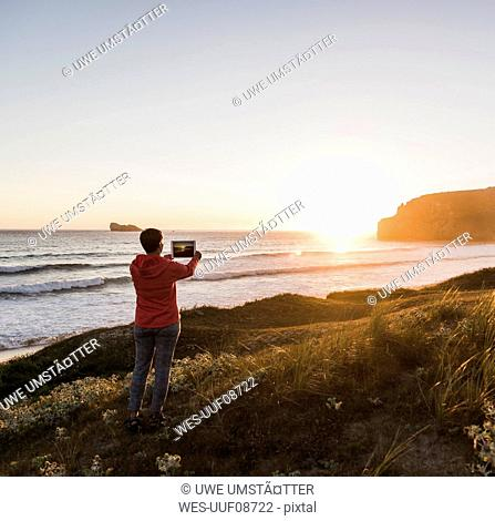 France, Bretagne, Crozon peninsula, woman at the coast at sunset taking picture with tablet