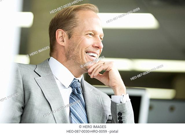 attractive businessman relaxed and smiling at the office