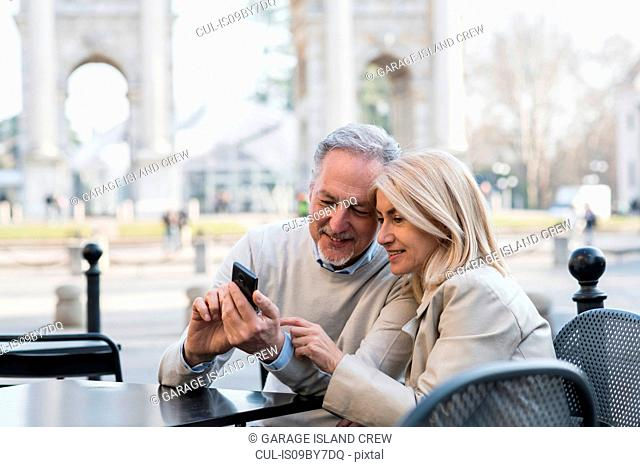 Senior couple using smartphone at cafe in city, Milan, Lombardia, Italy