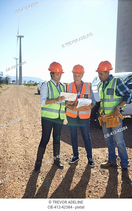 Engineer and workers using digital tablet at wind turbine power plant