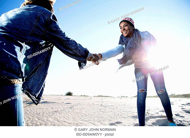 Two friends fooling around at beach, holding hands, smiling