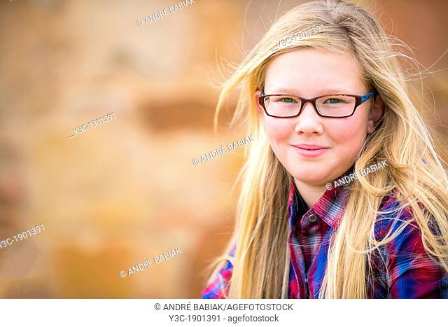 USA, Texas, Portrait of girl (12-13) with long blond hair and glasses