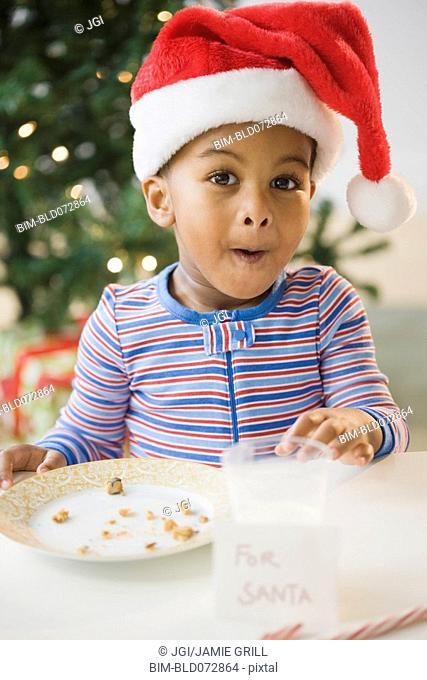 African American boy pointing to eaten cookies by 'For Santa' sign