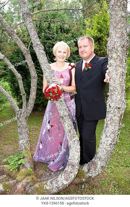 Happy Caucasian Wedding Couple by Pine Tree Trunk