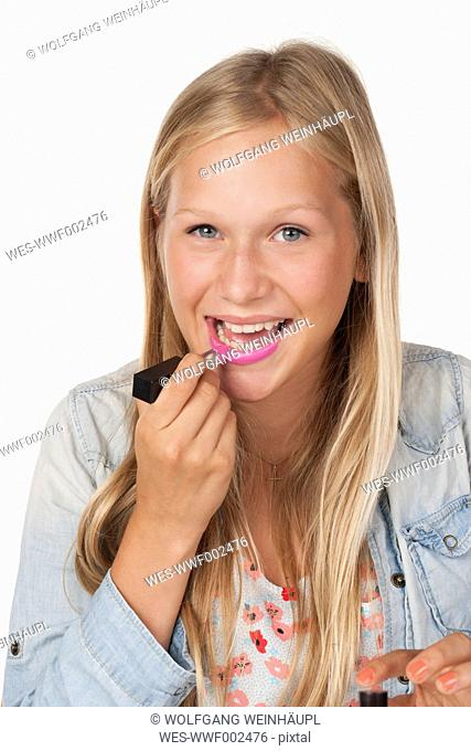 Teenage girl applying pink lipstick, close up