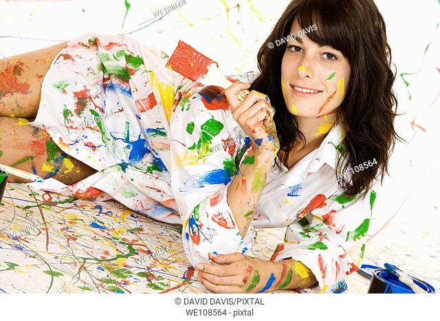 Woman in mid 20s having fun making a mess painting