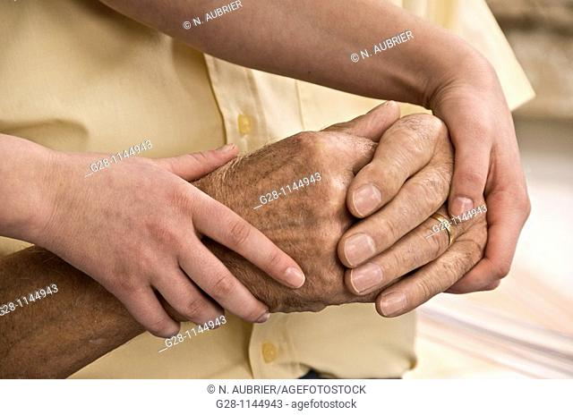 young person hands helping and comforting a senior man by holding his hands