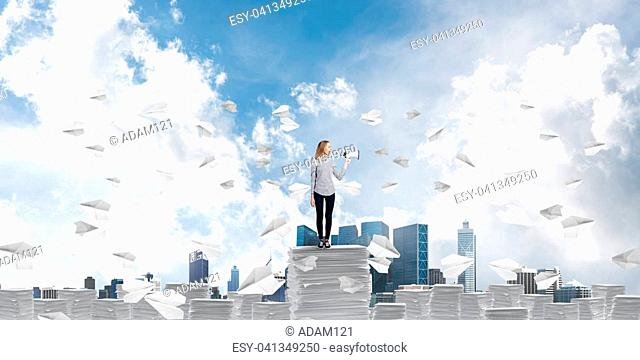 Woman in casual clothing standing among flying paper planes with speaker in hand and with skyscape on background. Mixed media