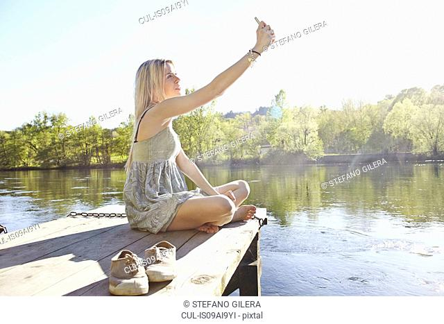 Young woman sitting on jetty photographing herself