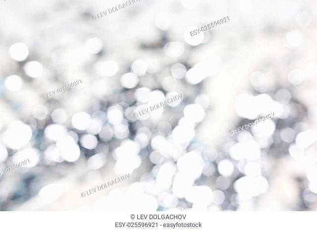 holidays, luxury and background concept - blurred silver christmas lights bokeh