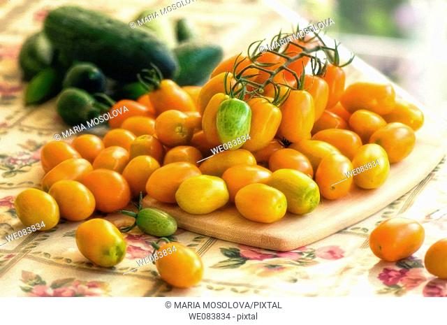 Freshly Harvested Orange Cherry Tomatoes and Green Cucumbers on Cutting Board. Solanum lycopersicon, cucumis sativus