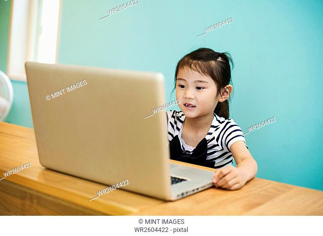 A young girl seated at a laptop computer in a classroom