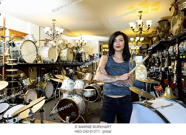 Portrait confident music shop owner holding drumsticks