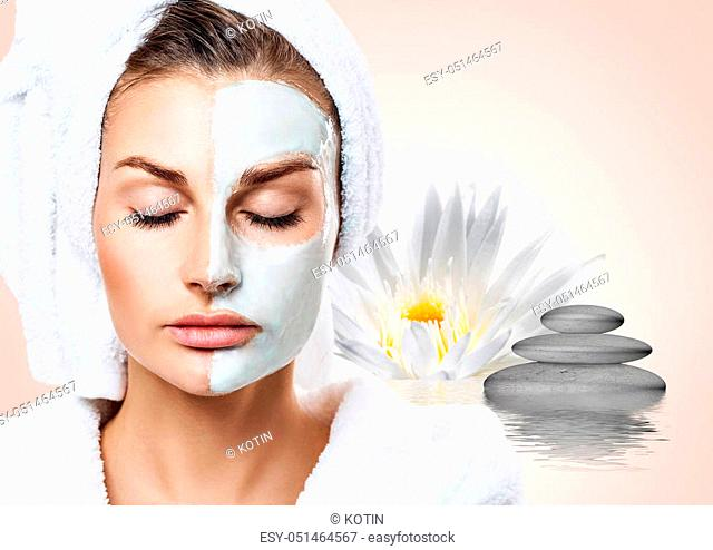 Beautiful woman with towel on head in ripple water with lotus flower. Spa concept. Over beige background