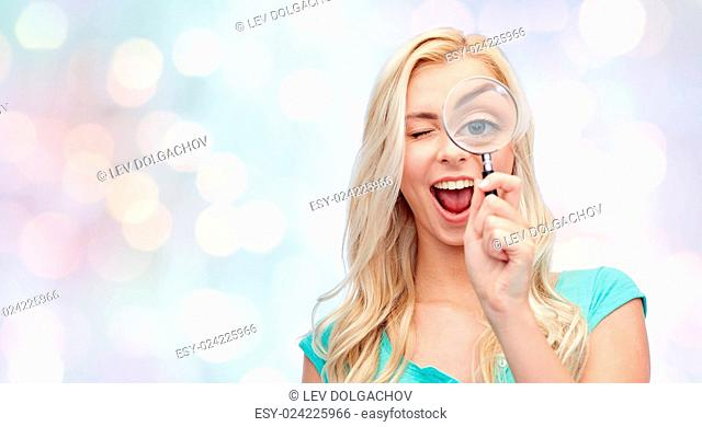 vision, exploration, investigation, education and people concept - happy smiling young woman or teenage girl looking through magnifying glass over holidays...
