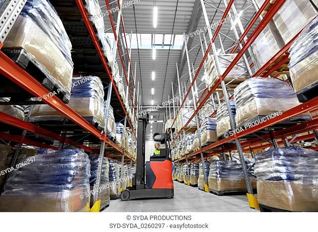 male loader operating forklift at warehouse