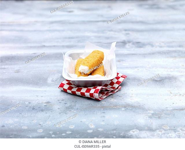 Fried chunky cod fish fingers in baking tin on steel table