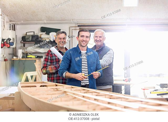 Portrait smiling male carpenters working at wood boat in workshop