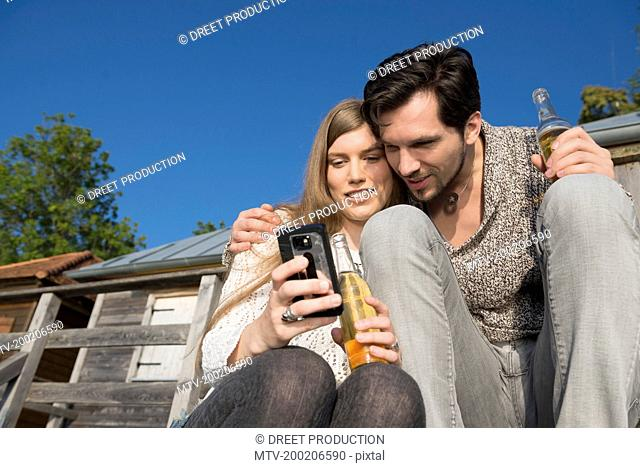 Man woman cell phone SMS drinking beer