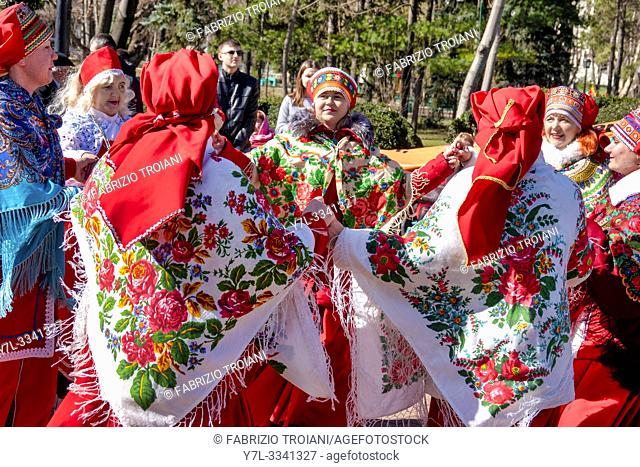 Dancers in traditional Moldovan dress dance during the festival of Maslenitsa, an eastern slavic religious and folk holiday, in ChiÈ. inau, Moldova