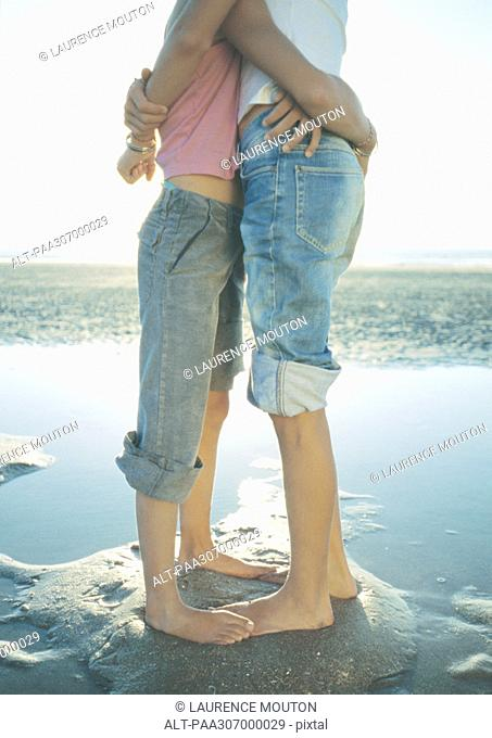 Two children standing on beach, embracing