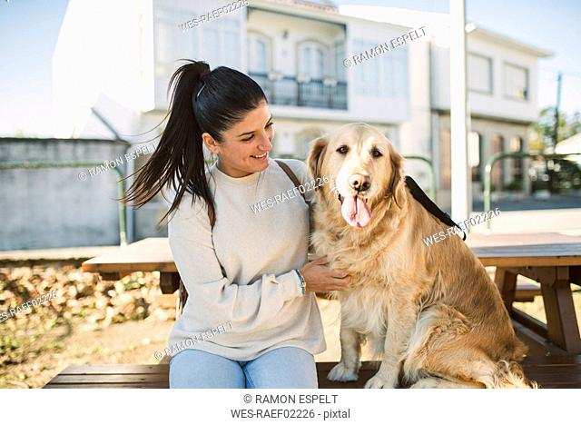 Smiling young woman with her Golden retriever dog resting outdoors