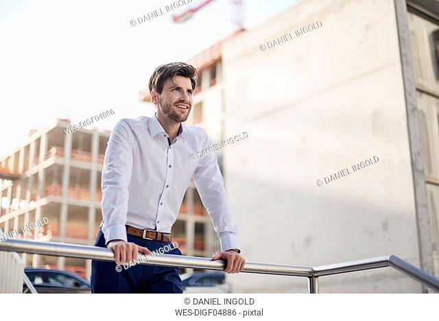 Portrait of smiling businessman in the city leaning on railing