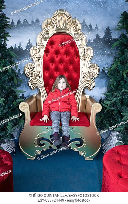 Portrait of four years old child with red coat looking at and sitting on a golden throne, in winter christmas holidays