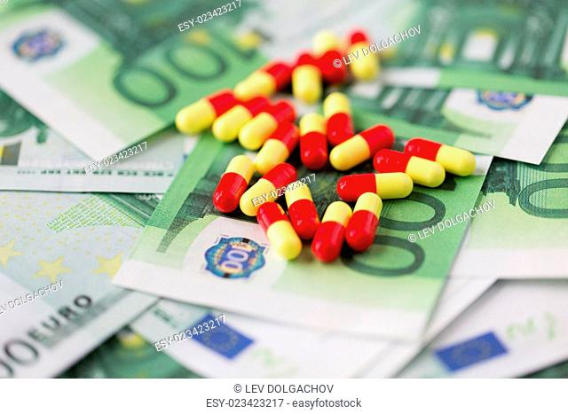 medicine, finance, health care and drug trafficking - medical pills or drugs and euro cash money on table