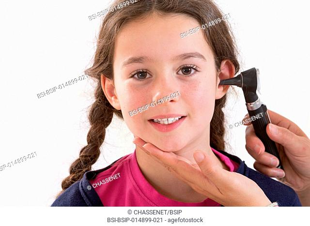Doctor examining the ear of a girl