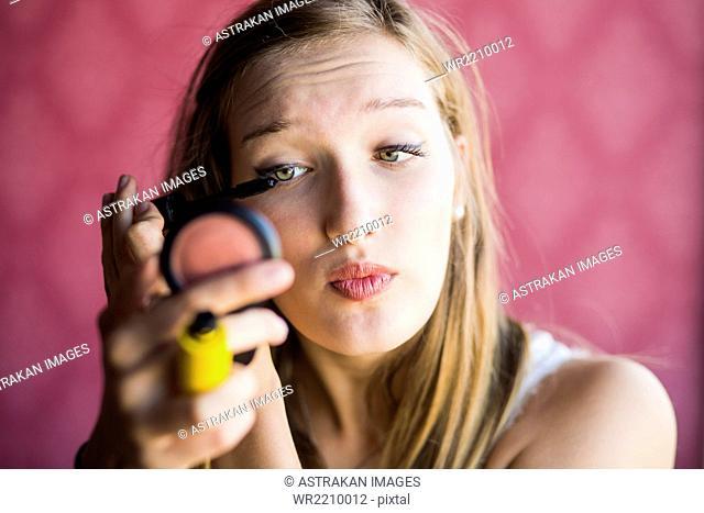 Teenage fashion model applying mascara in studio