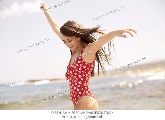 Young woman at beach, one piece swimsuit. Crete, Greece