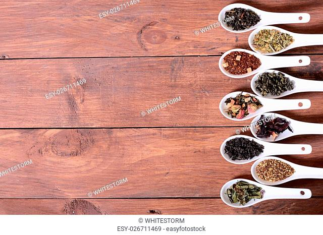assortment of dry tea in ceramic bowls on wooden background
