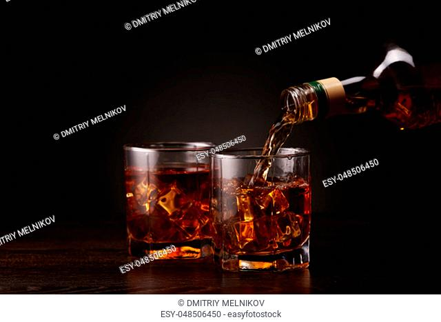 Pouring whiskey from a bottle into glass with ice standing on a dark table on a black background