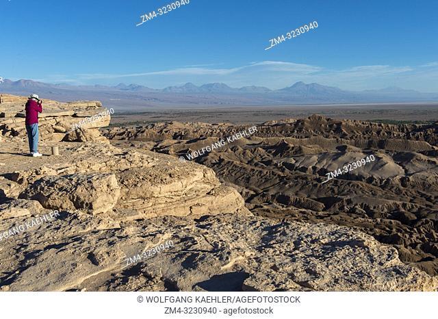 A woman is photographing the Valley of the Moon near San Pedro de Atacama in the Atacama Desert, northern Chile