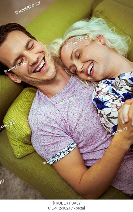 Affectionate laughing couple laying on sofa with eyes closed