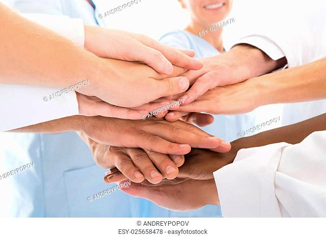 Cropped image of medical team stacking hands against white background