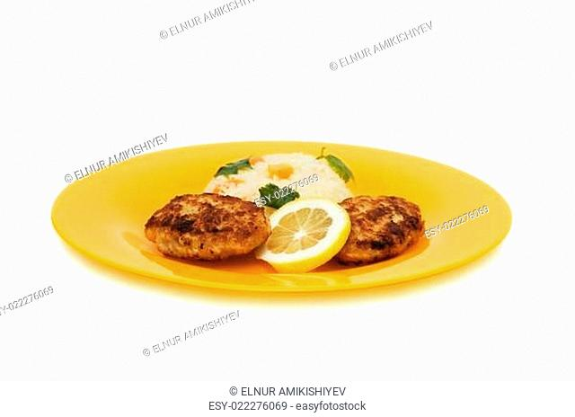 Cutlets, rice and lemon on the plate isolated