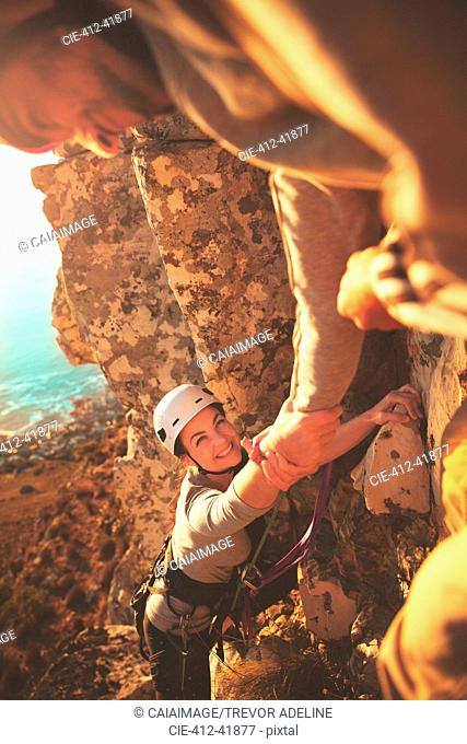 Smiling female rock climber reaching for hand
