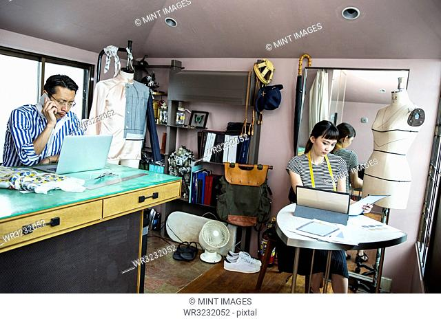 Japanese male and female fashion designers working in a studio