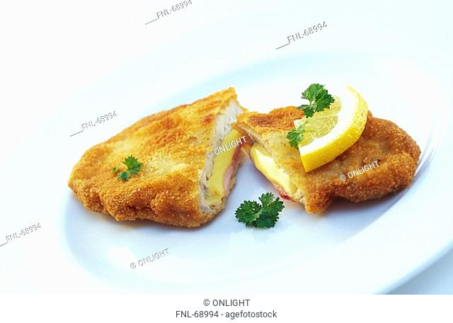 Close-up of schnitzel and slice of lemon on plate