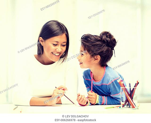 family, children and happy people concept - mother and daughter drawing