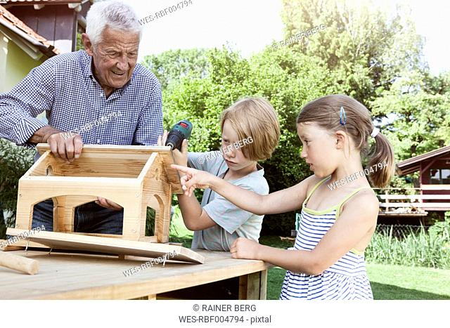 Grandfather and grandchildren building up a birdhouse