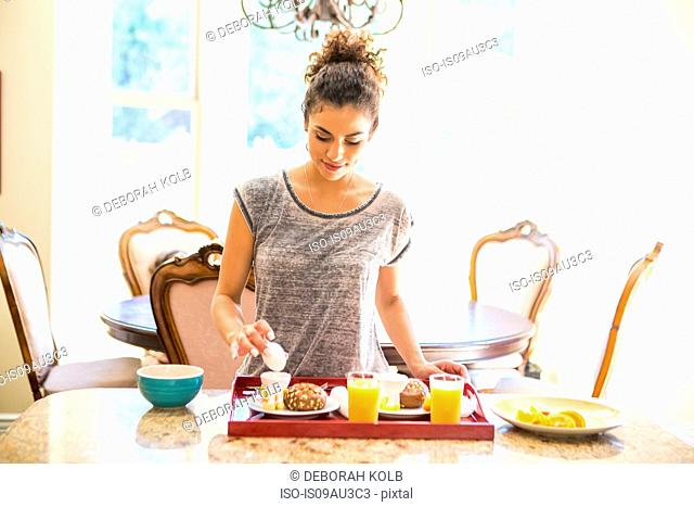Young woman at home preparing breakfast tray, looking down holding egg