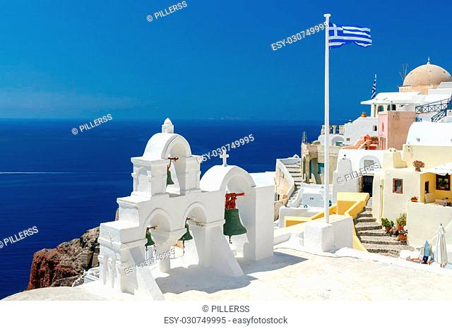 White tower with bells and the Greek flag on a background of blue sea and sky in the village of Oia. Santorini, Greece